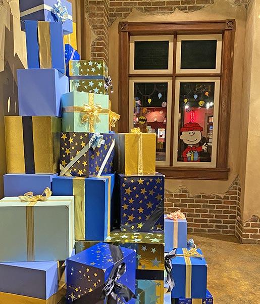 クリスマスプレゼントと外からチャーリーブラウンが覗いている